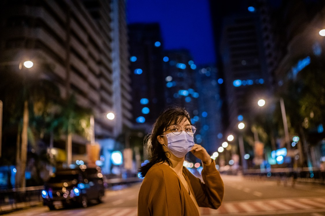 Young women with mask in city at night
