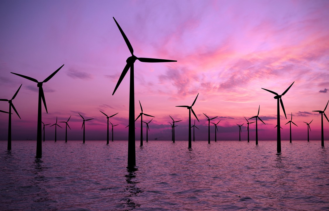 Offshore windmills in the ocean and sunset in the background