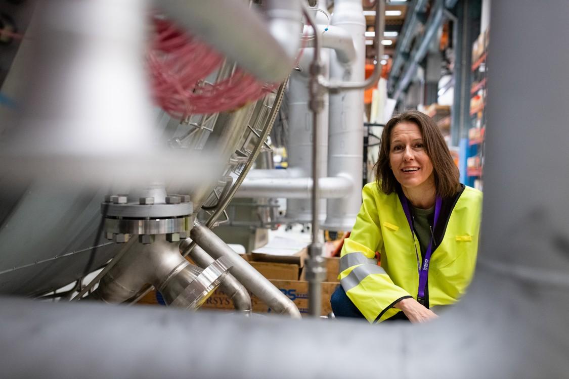 Åsa Lyckström next to an SGT-800 gas turbine in the assembly workshop, Finspång, Sweden