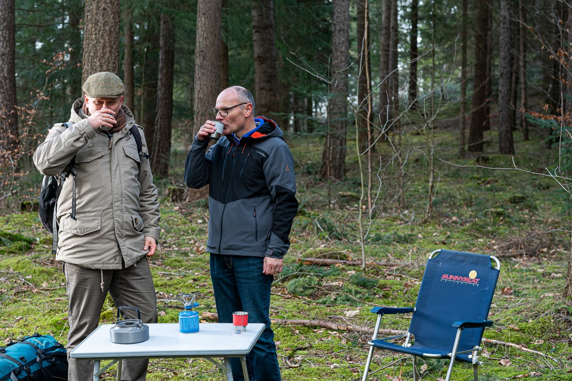 Wolfgang Klink and Christopher Findlay drink hot tea cooked on a camping stove