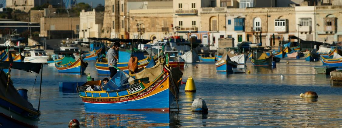 vista de uma das baias de malta com barcos coloridos e casas ao fundo