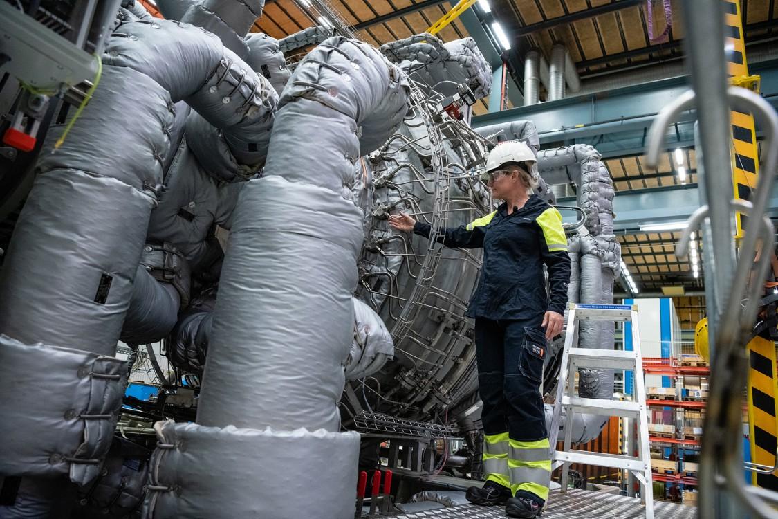 Senior Expert in Combustion Technology Jenny Larfeldt examines a gas turbine ahead of a hydrogen test