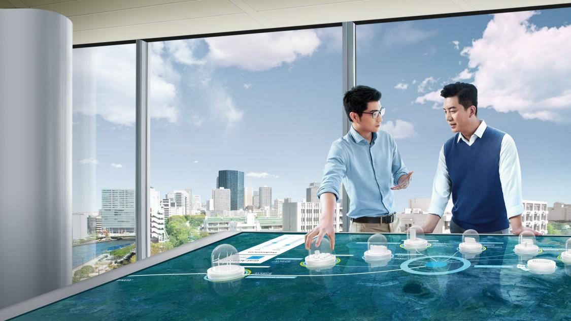 dois homens estão em um escritório diante de uma mesa tecnológica que destaca cidades