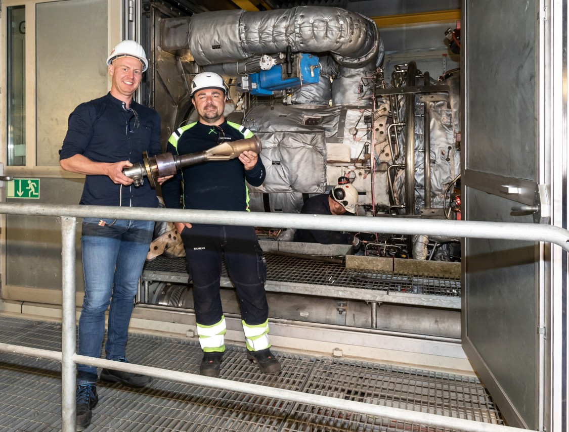 Niklas Lange, project manager at E.ON Energy Services, and Siemens Energy engineer Emir Basic holding a 3D-printed burner in front of its gas turbine at the potash plant in Philippsthal, Germany.