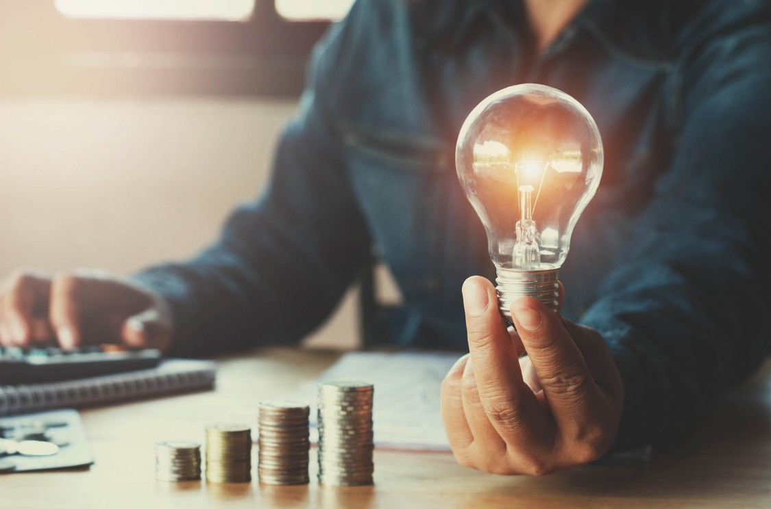 Man holding a lightbulb with a stack of coins next to him symbolizes the economic benefits offered by hybrid power solutions in remote locations