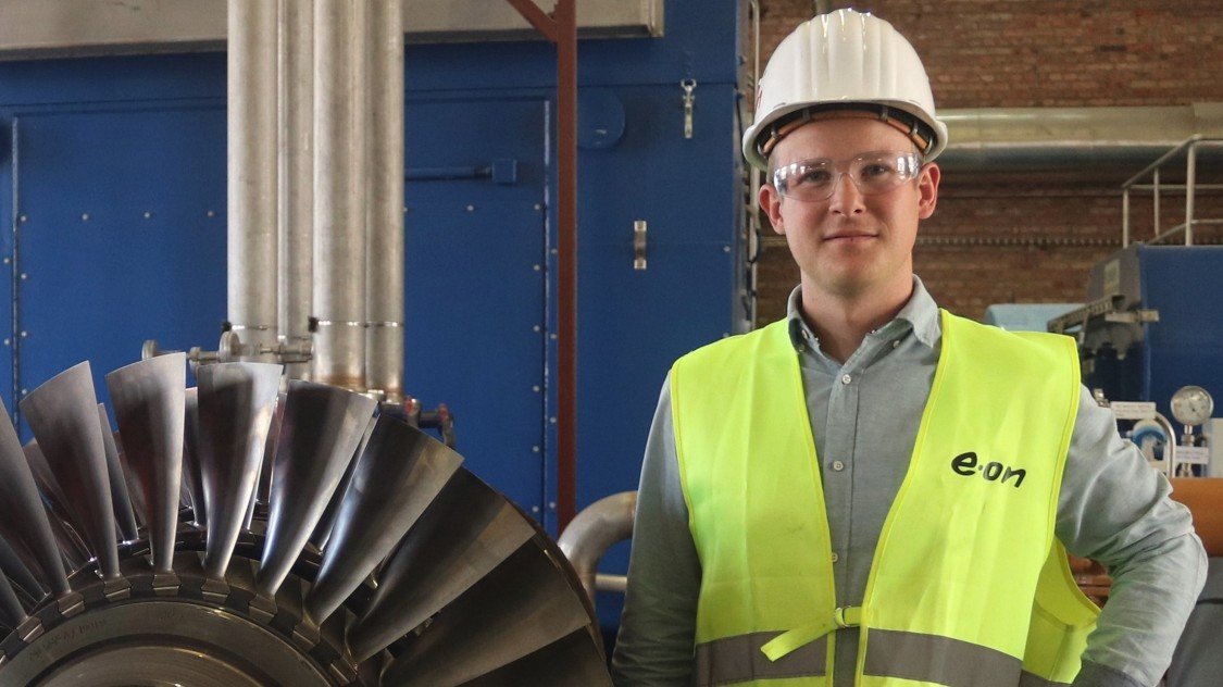 obias Müller standing next to a gas turbine from Siemens Energy