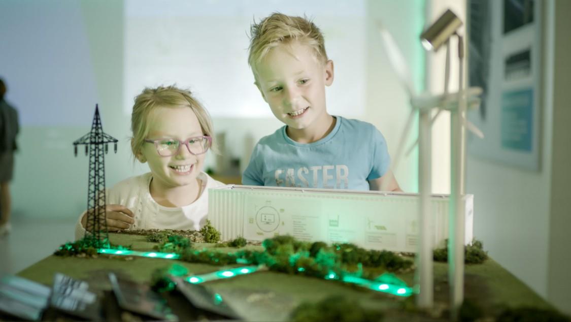 duas crianças estão felizes observando uma maquete de uma usina elétrica